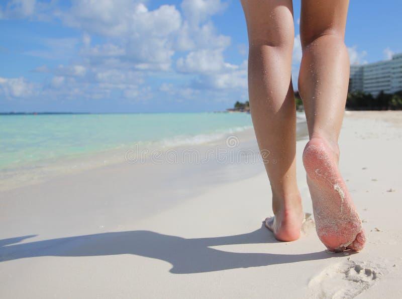 在热带沙子的性感的腿靠岸与脚印。 库存照片