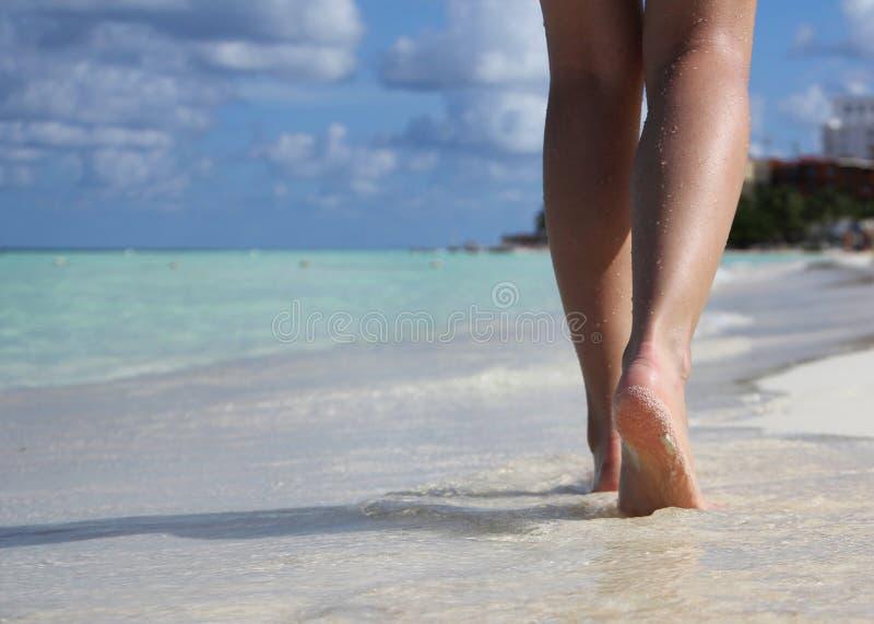 在热带沙子的性感的腿靠岸与脚印 图库摄影