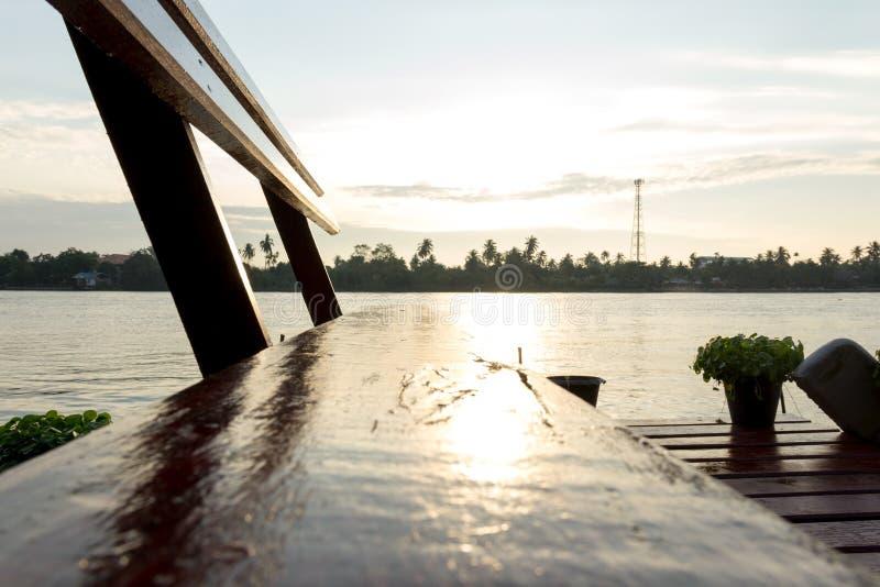 在热带河沿的长木凳 免版税库存图片