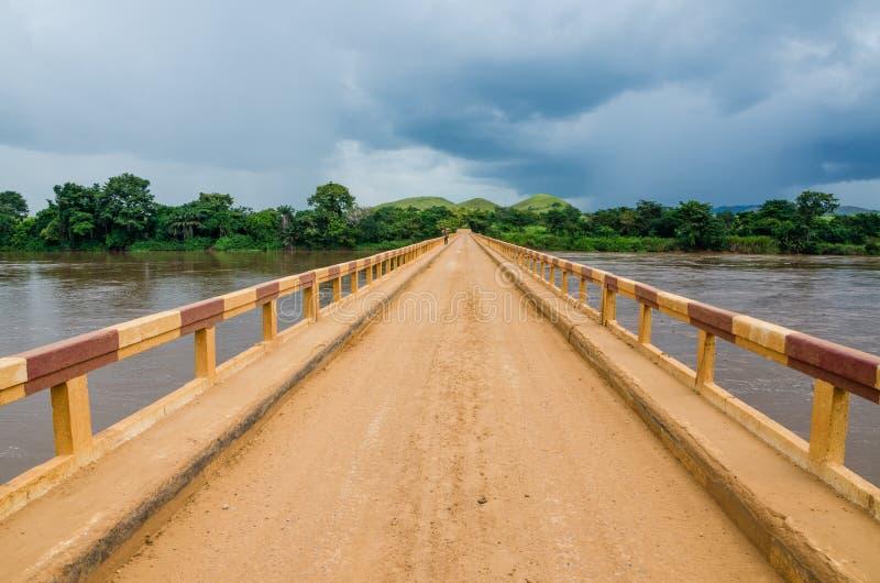 在热带河的简单的土路桥梁有剧烈的云彩的在刚果共和国,非洲 免版税库存照片