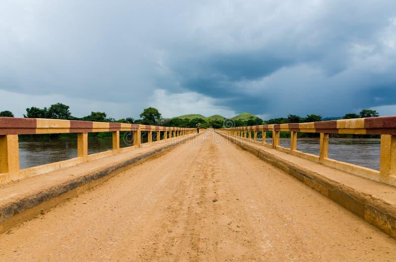 在热带河的简单的土路桥梁有剧烈的云彩的在刚果共和国,非洲 免版税库存图片