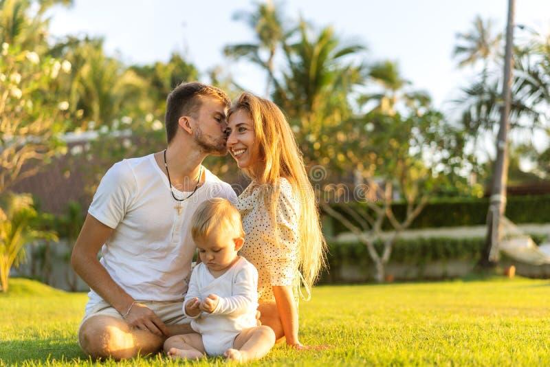 在热带海岛上的幸福家庭使用与儿子的日落的 图库摄影