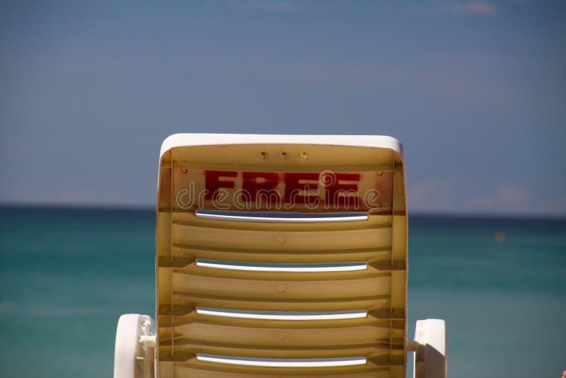 在热带海岛上的自由孤立海滩椅子有在天际的全景在绿松石水,普吉岛,泰国 图库摄影