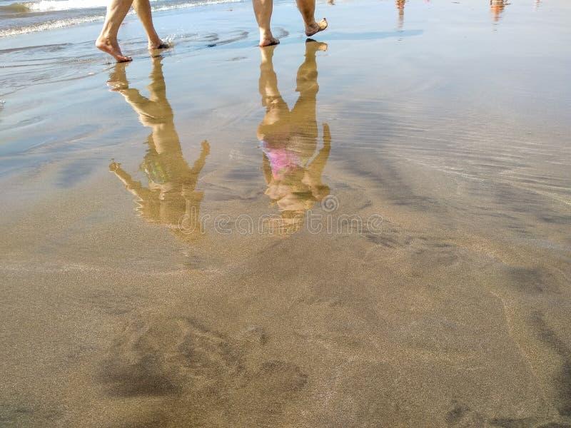 在热带海滨的海滩的沙子的水的反射在显示几个人的脚的低潮期间的 图库摄影