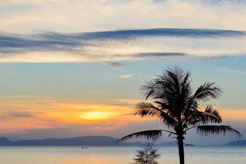 在热带海滩和可可椰子树和渔夫小船的日落 库存照片