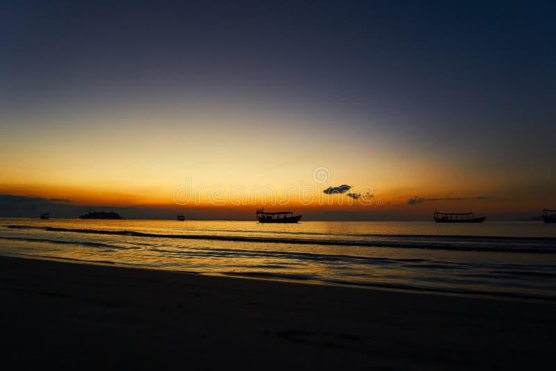 在热带海滩酸值rong柬埔寨,与longtail小船的风景的日出,当太阳上升时 库存图片