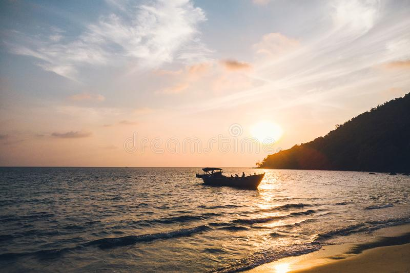 在热带海滩酸值rong柬埔寨,与longtail小船的风景的日出 免版税库存照片