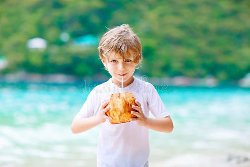在热带海滩的小孩男孩饮用的椰子汁 免版税图库摄影
