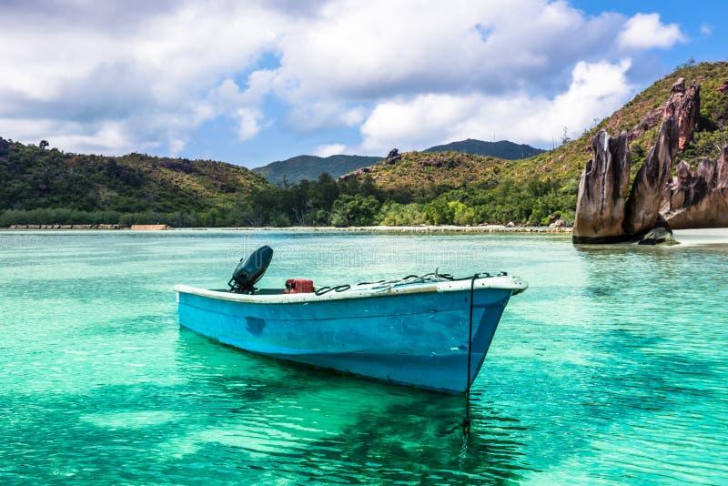 在热带海滩的老渔船在Curieuse海岛塞舌尔群岛 免版税图库摄影