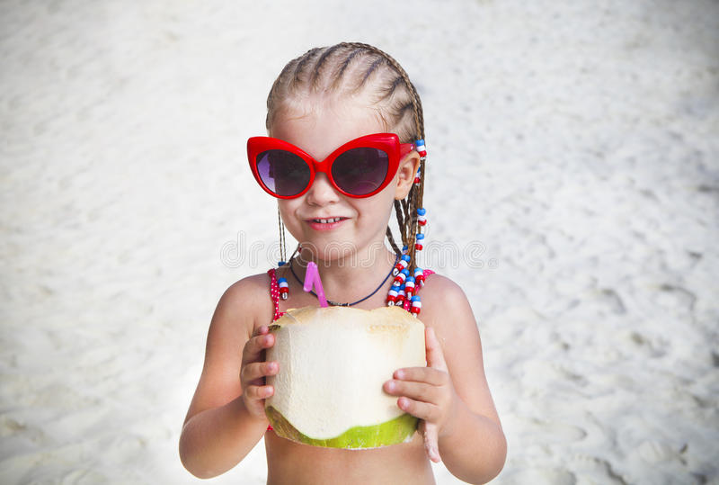 在热带海滩的逗人喜爱的小女孩饮用的椰子鸡尾酒 库存照片