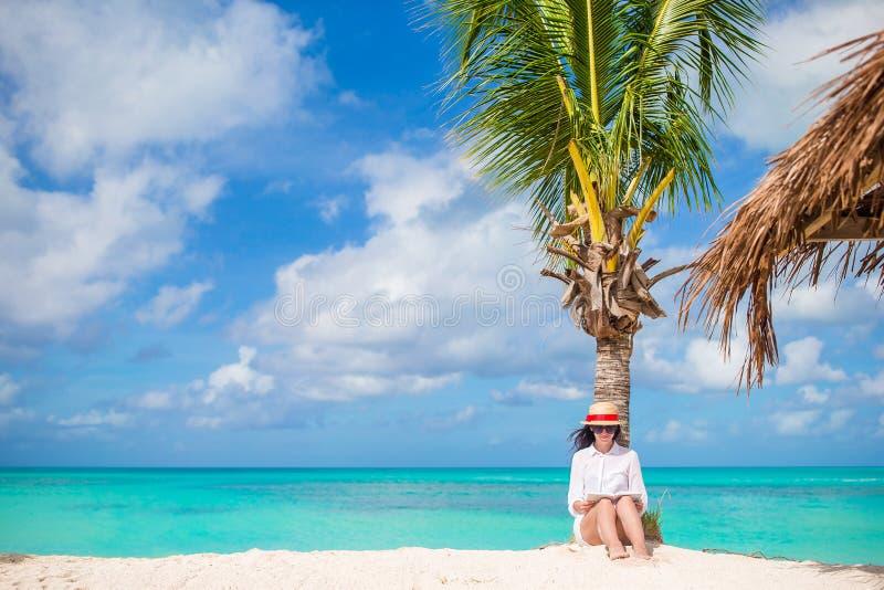 在热带白色海滩的少妇读书在棕榈树附近 库存照片