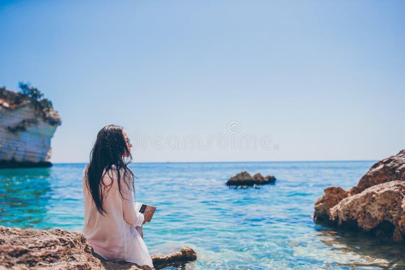 在热带白色海滩的年轻女人读书 库存照片