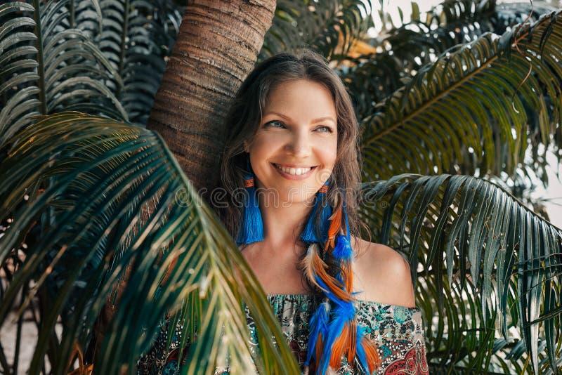 在热带背景的美丽的年轻smilling的妇女画象 图库摄影