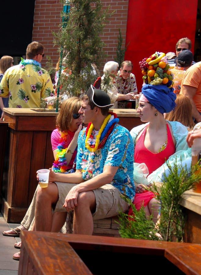 在热带衣物穿戴的家庭 妇女在她的头的wth果子坐与其他党行人在P&L区坎萨斯城Mo美国 免版税库存照片