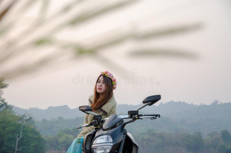 在热带领域的亚洲妇女骑马摩托车 库存照片