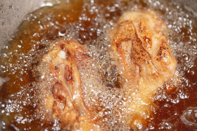 在热油的炸鸡和煮沸在平底锅 图库摄影