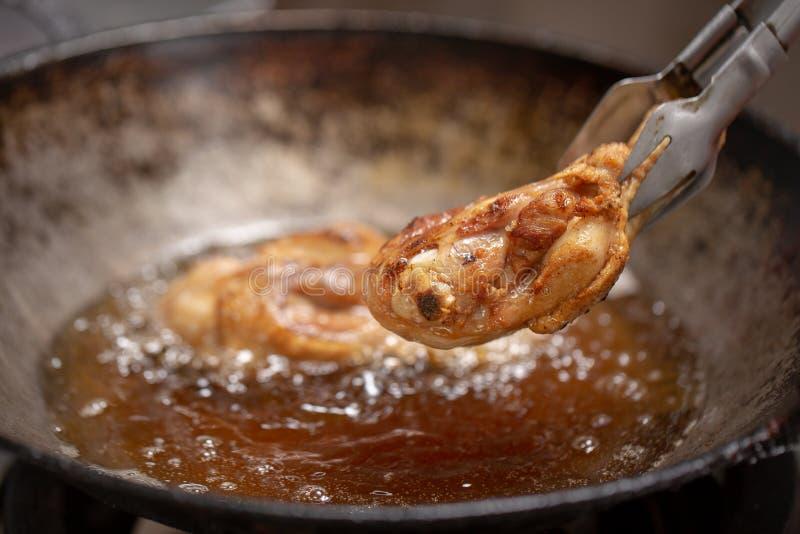 在热油的炸鸡和煮沸在平底锅 库存图片