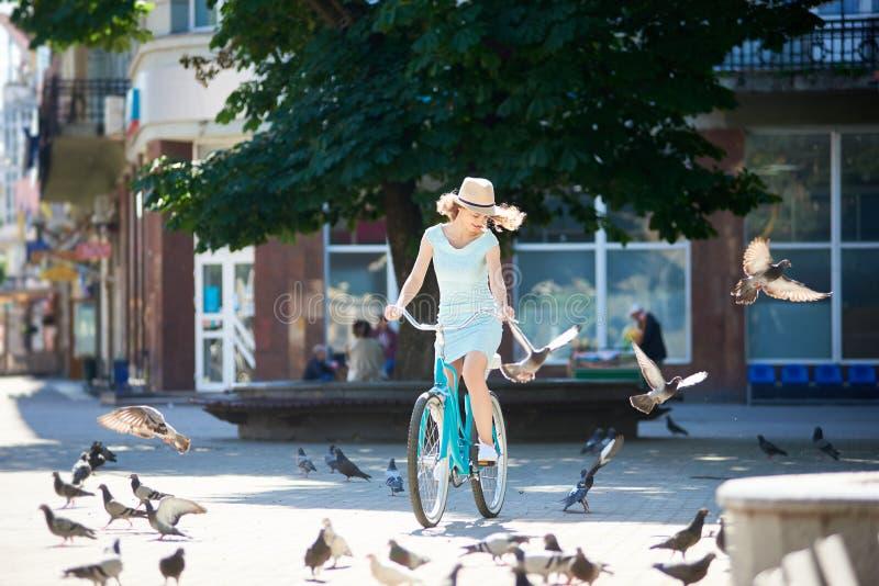 在热的夏日期间,骑蓝色葡萄酒自行车在被铺的市中心的草帽的正面女孩追逐鸽子聚集 库存图片