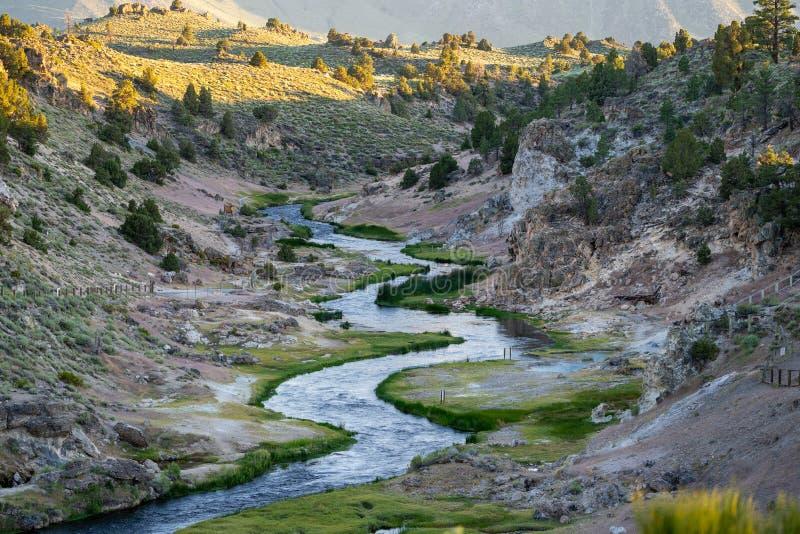 在热的小河地质站点的日落在马麦斯湖,陈列绞的起泡的河、温泉城和火山运动  库存图片