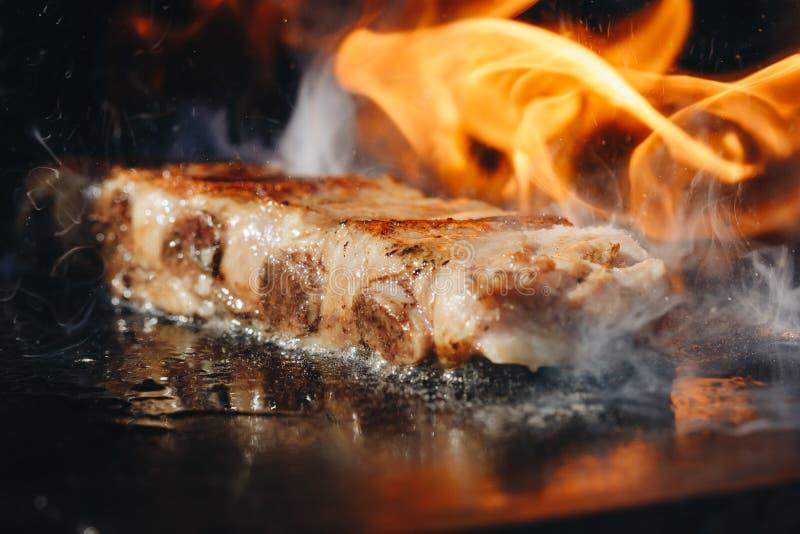在热的火焰状格栅背景的BBQ烘烤用卤汁泡的婴孩后面排骨特写镜头 免版税库存图片