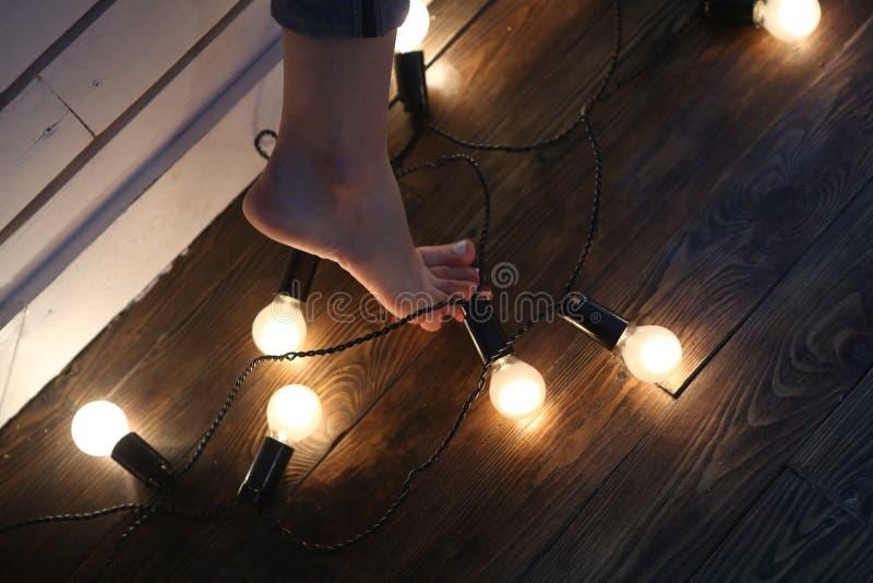 在热的灼烧的减速火箭的灯中的赤足女性脚 库存图片
