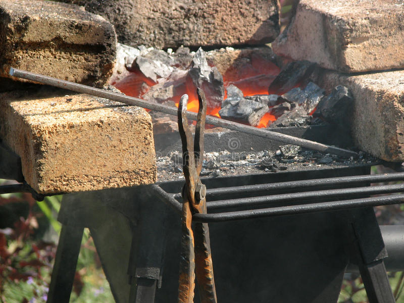 在热的煤炭背景的史密斯工具  免版税库存照片