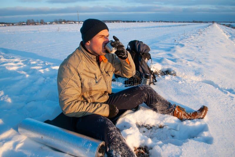在热的茶观看日落,咖啡在一个冬日,冒险概念室外活动的一杯的游人 冬天 免版税库存照片