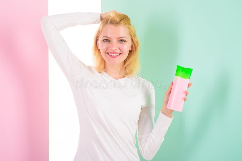 在热称呼前保护头发 应用防护称呼技巧的产品第一根头发 女孩金发碧眼的女人拿着香波瓶 库存图片