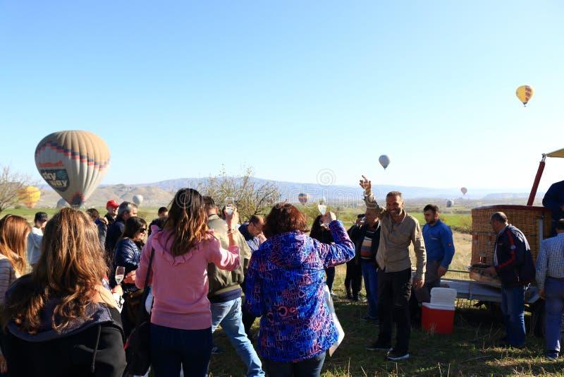 在热空气气球以后的愉快的游人游览卡帕多细亚土耳其 免版税库存图片