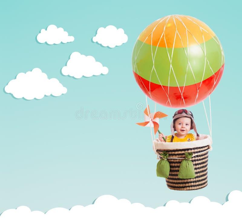 在热空气气球的逗人喜爱的孩子在蓝天 免版税图库摄影