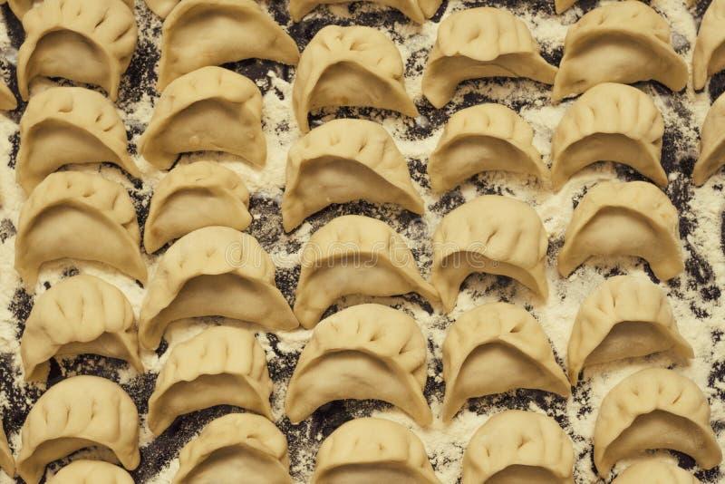 在烹调前的饺子pelmeni 俄国烹调背景上面 免版税库存照片