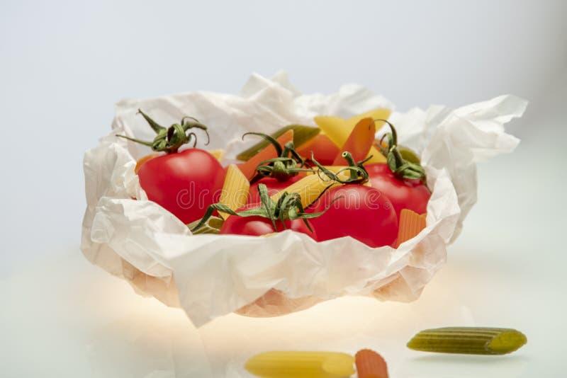 在烹调在红色背景的纸和色的面团包裹的蕃茄 免版税图库摄影