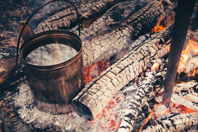在烹调在natur的铸铁大锅的营火的大罐 免版税库存图片