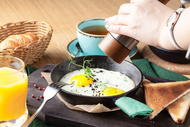 在烹调平底锅的游人的英式早餐有荷包蛋、香肠、烟肉、多士和咖啡的 图库摄影