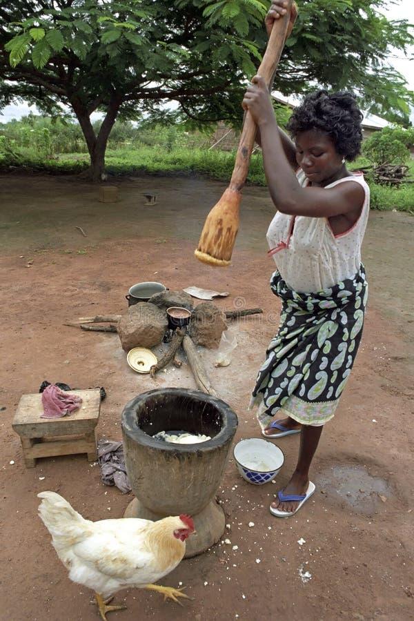 在烹调期间的加纳的妇女,捣碎的食物 免版税图库摄影