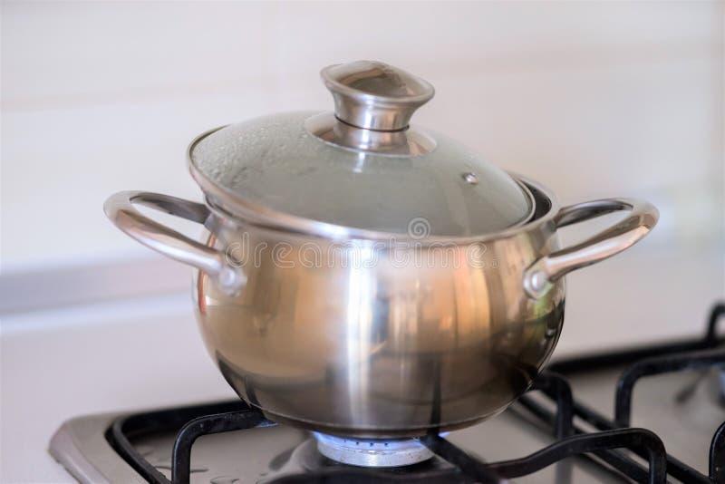 在烹调的不锈钢平底锅在煤气炉期间 免版税库存照片