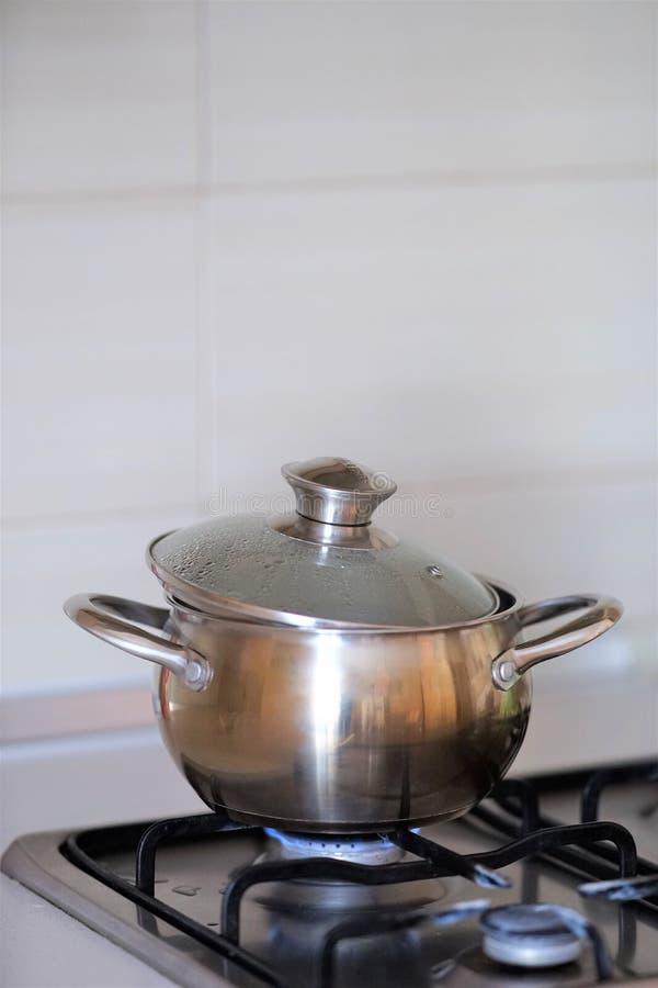 在烹调的不锈钢平底锅在煤气炉期间 库存图片