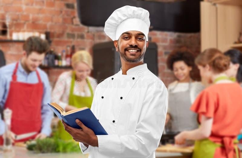 在烹饪课的男性印度厨师读书菜谱 免版税库存图片
