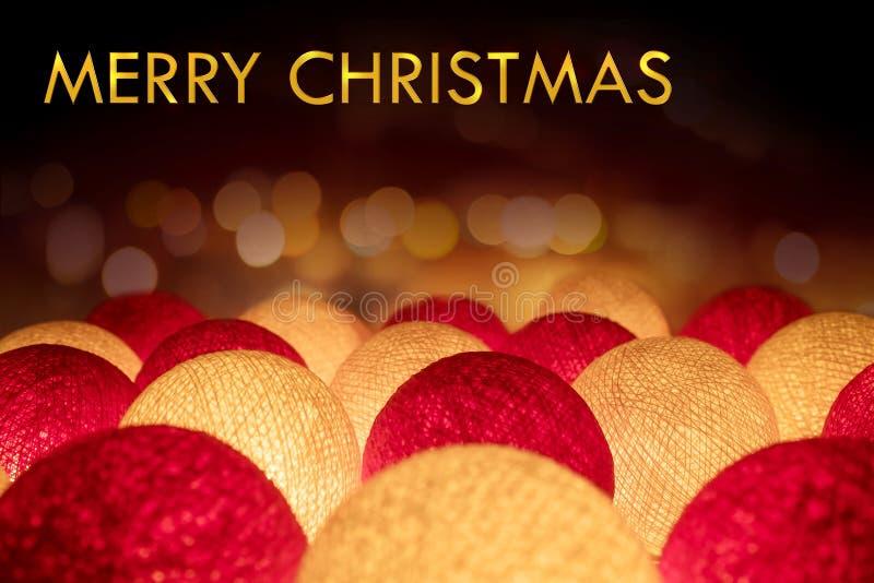 在焕发的金黄圣诞快乐在深红和白光球 库存图片