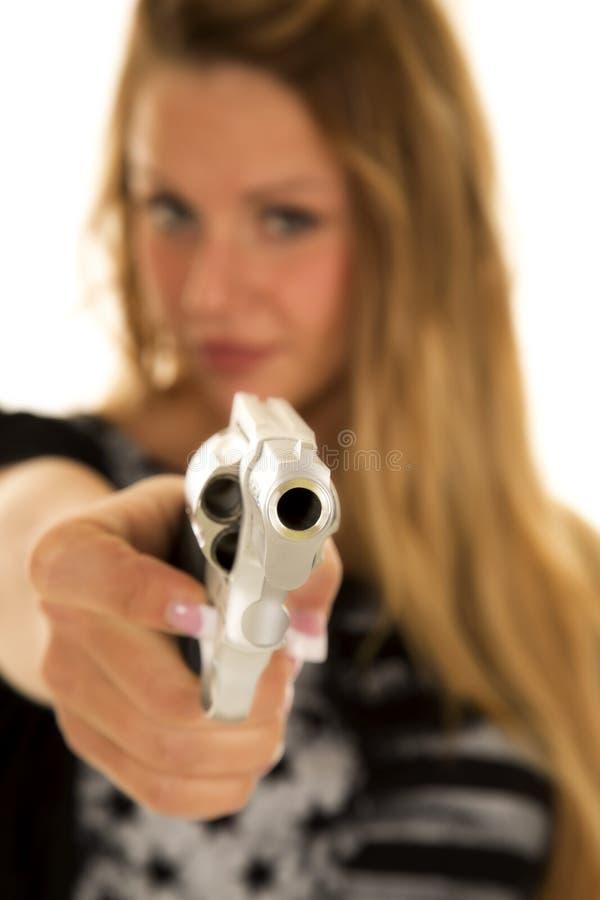 在焦点外面的妇女在一把针对性的手枪后 免版税库存图片