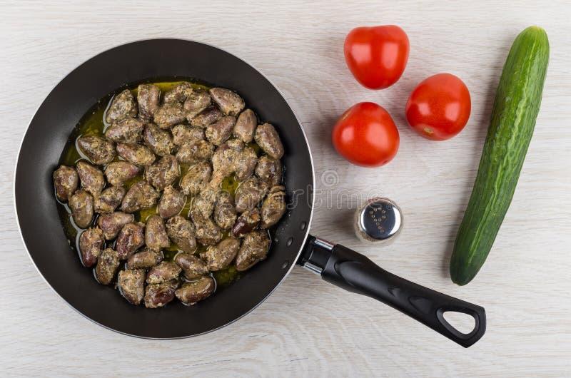 在煎锅、胡椒、黄瓜和tomatoe的炸鸡心脏 免版税库存照片