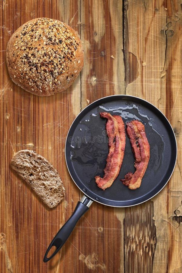 在煎锅有面包切片的和大面包的烟肉更卤莽在老过时木表上 免版税库存照片