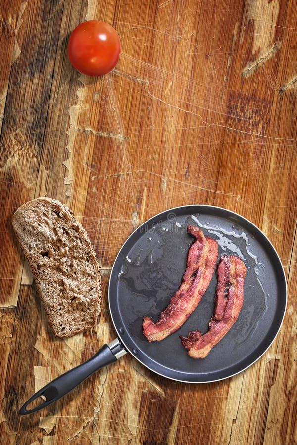 在煎锅有面包切片的和蕃茄的烟肉更卤莽在老过时木表上 库存照片