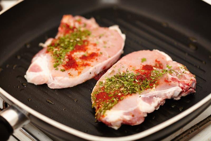 在煎锅的加香料的未加工的猪排 免版税库存照片