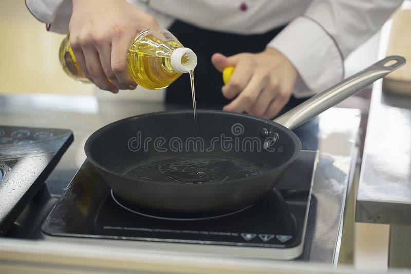 在煎锅的厨师倾吐的油 去的手套的男性厨师油煎准备肉的鸭胸脯厨师 免版税库存图片