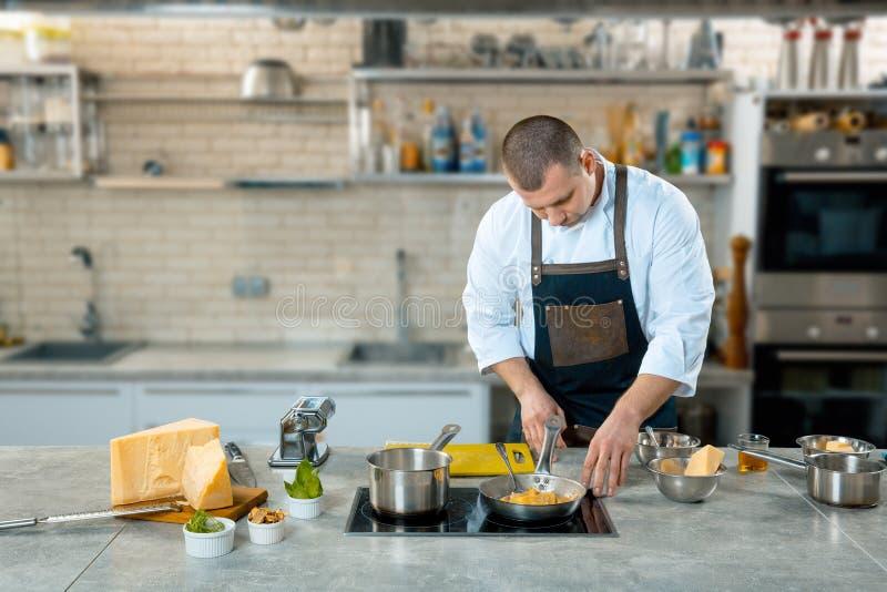 在煎锅的厨师油炸物意大利食物 库存图片
