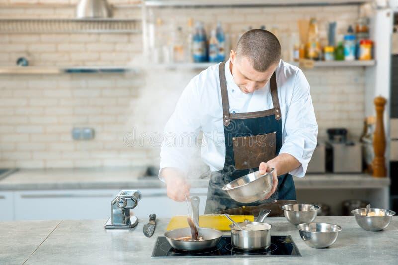 在煎锅的厨师油炸物意大利食物 免版税库存图片