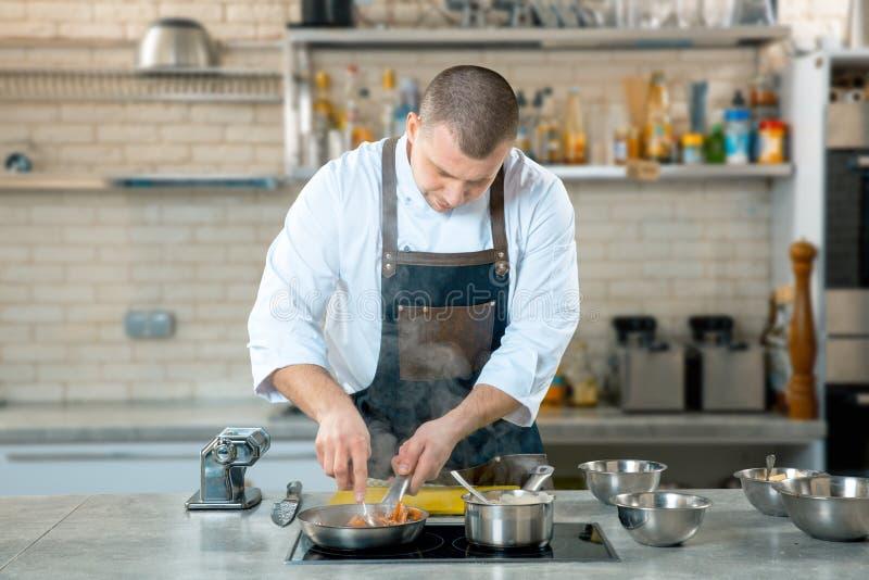 在煎锅的厨师油炸物意大利食物 库存照片