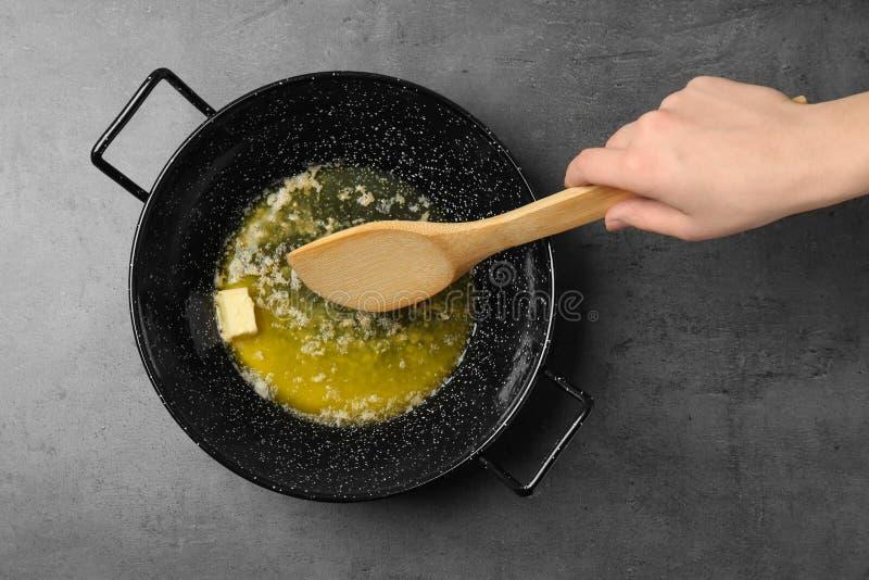 在煎锅的妇女混合的熔化的黄油在灰色背景 免版税库存图片