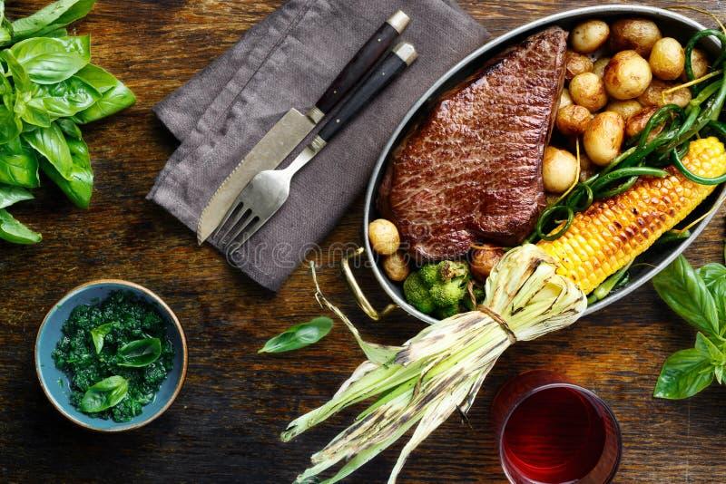 在煎锅的水多的牛排有菜和红葡萄酒的 免版税库存图片